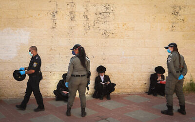 Police officers close synagogues and hand out fines in the city of Beit Shemesh to ultra-Orthodox Jews who violated coronavirus regulations, April 16, 2020. (Yaakov Lederman/Flash90)