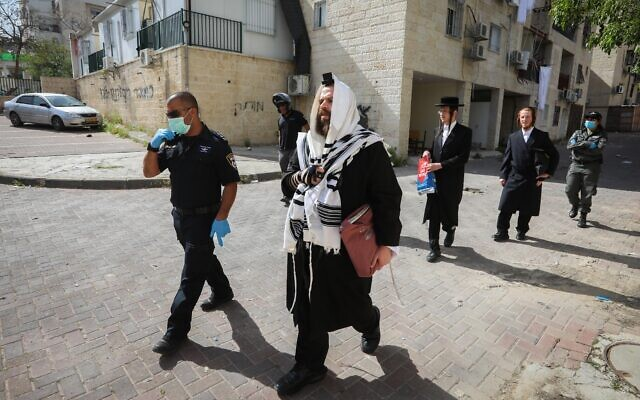 Illustrative: Police officers close synagogues and hand out fines to ultra-Orthodox Jews in the city of Beit Shemesh for violating coronavirus guidelines, April 16, 2020. (Yaakov Lederman/Flash90)