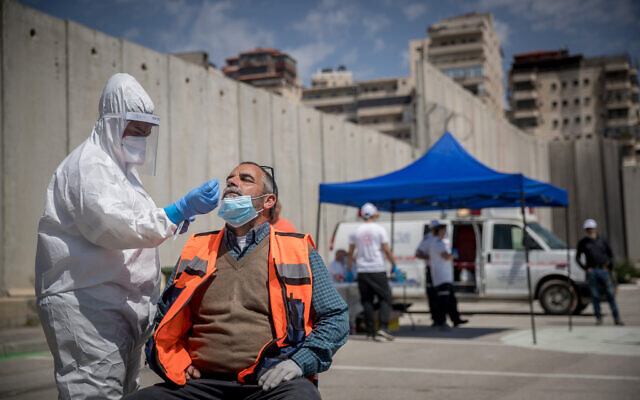 Magen David Adom medical workers seen at a drive-through site to collect samples for coronavirus testing, alongside the security barrier outside Shuafat Refugee Camp, Jerusalem, April 16, 2020. (Yonatan Sindel/Flash90)