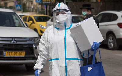 A Magen David Adom ambulance service medic, wearing protective gear, seen handling coronavirus tests from patients outside a hotel being used as a coronavirus quarantine facility, in Jerusalem on April 19, 2020. (Nati Shohat/Flash90)