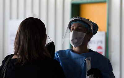 A Shaare Zedek Medical team member wearing protective gear takes a swab from a woman to test for the coronavirus disease (COVID-19), outside the coronavirus unit at Shaare Zedek hospital in Jerusalem on April 20, 2020. (Nati Shohat/Flash90)