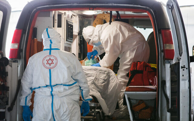 Magen David Adom medics wearing protective clothing evacuate a suspected coronavirus patient to the coronavirus unit at Shaare Zedek hospital in Jerusalem, April 20, 2020. (Nati Shohat/Flash90)