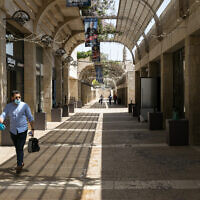 A man walks past closed stores in the Mamilla Mall in Jerusalem on April 22, 2020. (Olivier Fitoussi/Flash90)
