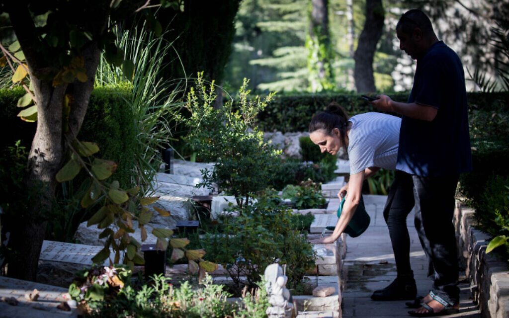 A woman visits the grave of a family member at the military cemetery on Mount Herzl in Jerusalem on April 22, 2020. (Photo by Yonatan Sindel/Flash90)