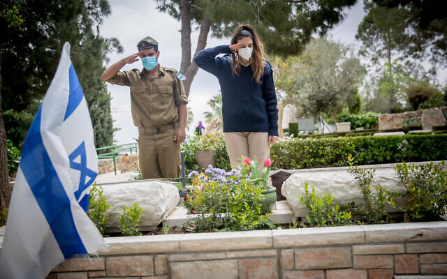 IDF troops salute at the grave of a soldier at Mount Herzl military cemetery in Jerusalem on April 24, 2020. (Yonatan Sindel/Flash90)
