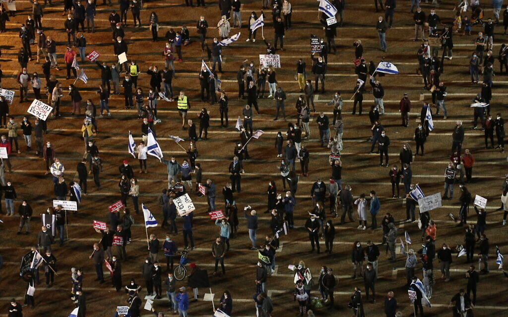 Keeping a 2-meter distance from each other, thousands of protesters attend a 'black flag' demonstration in Tel Aviv on Saturday, April 25, 2020. (Miriam Alster/Flash90)