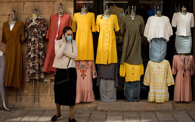 A woman wearing a protective face mask walks past a clothes shop in Jerusalem on April 26, 2020. (Nati Shohat/Flash90)