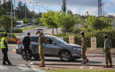 Israeli police and soldiers guard at a roadblock at the entrance to a neighborhood in the city of Beit Shemesh on April 26, 2020. (Yaakov Lederman/Flash90)
