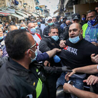Store owners at Jerusalem's Mahane Yehuda market scuffle with police during a protest over the continued closure of open-air markets, April 25, 2020. (Yonatan Sindel/Flash90)