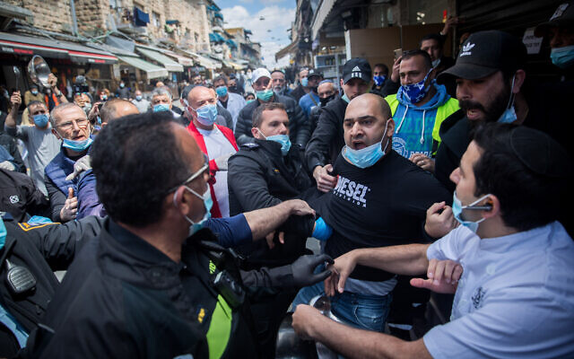 Police arrest a man during a protest by stall-owners at the Mahane Yehuda market in Jerusalem against the ongoing closure of their businesses, April 26, 2020. (Yonatan Sindel/Flash90)