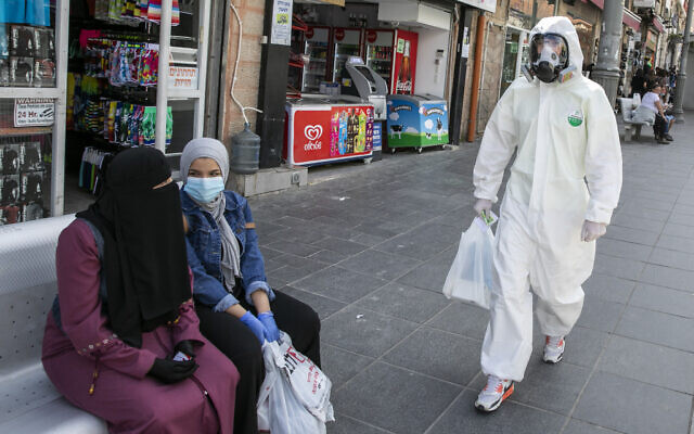 A man wearing a biological face mask and a protective suit does his shopping in downtown Jerusalem after the government eased some lockdown measures that it had imposed in order to stop the spread of the coronavirus, on April 27, 2020. (Olivier Fitoussi/Flash90)