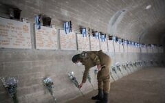 Israeli soldier places flowers and salute on graves of fallen Israeli soldiers, at Mount Herzl Military Cemetery on April 27, 2020.(Yonatan Sindel/Flash90)