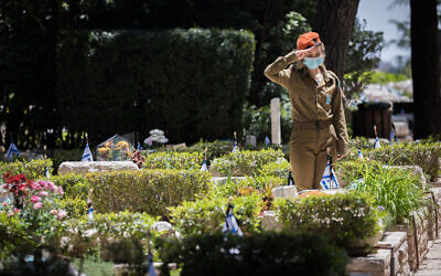 An Israeli soldier places flowers and salutes the graves of fallen Israeli soldiers, at Mount Herzl Military Cemetery in Jerusalem, on April 27, 2020. (Yonatan Sindel/Flash90)