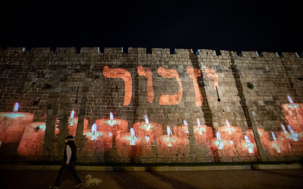 Names of fallen Israeli soldiers are screened on the walls of Jerusalem's Old City as Israel marks Memorial Day for the fallen soldiers and victims of terror, April 27, 2020. (Yonatan Sindel/Flash90)