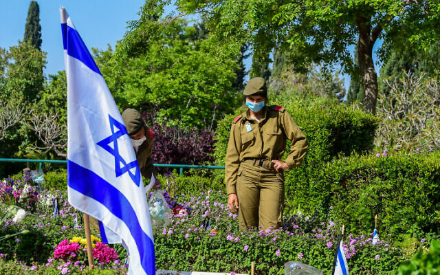 Israeli soldiers near the graves of fallen soldiers at the Kiryat Shaul Military Cemetery as Israel marks Memorial Day for the fallen soldiers and victims of terror on April 28, 2020. (Avshalom Sassoni/Flash90)