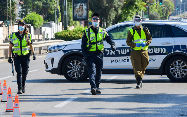 Israeli police and soldiers guard at a roadblock on a road leading to the Kiryat Shaul Military Cemetery, as Israel marks Memorial Day on April 28, 2020. (Avshalom Sassoni/Flash90)