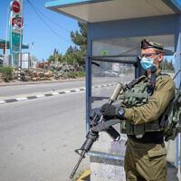 Illustrative: A soldier stands at a bus station at Gush Etzion Junction on April 28, 2020. (Gershon Elinson/Flash90)