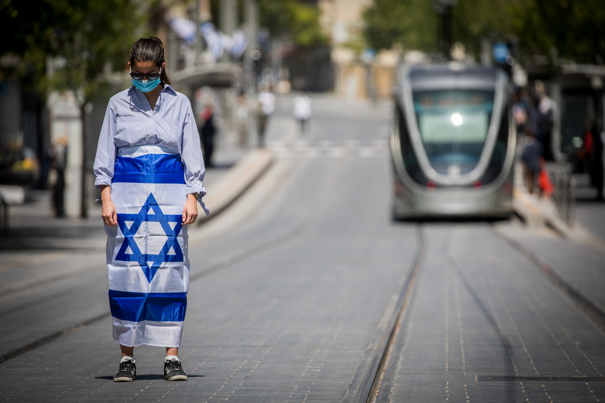 People stand for a two-minute silence in Jerusalem on Memorial Day, Yom Hazikaron, April 28, 2020. (Yonatan Sindel/Flash90)