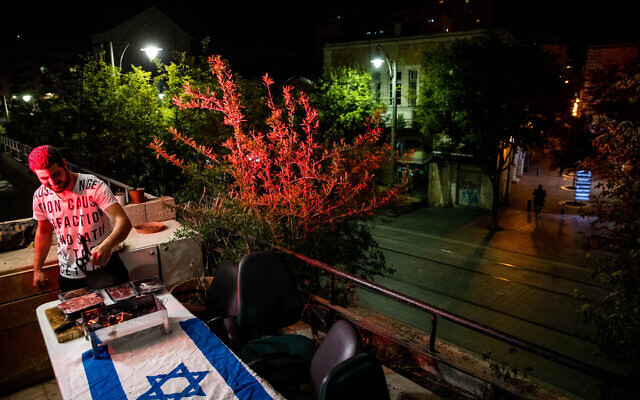 An Israeli cooking meat on a barbecue at his home on Jaffa Road in Jerusalem, as Israel celebrates its 72th Independence Day under lockdown, April 28, 2020.  (Yonatan Sindel/Flash90)