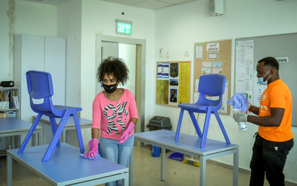 Workers clean a classroom at Luba Eliav primary school in Rishon Lezion on April 30, 2020. (Flash90)
