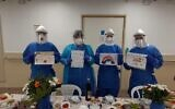 Medical personnel sit down for a Passover seder at Soroka Hospital in Beersheba on April 8, 2020. (Health Ministry)