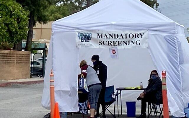 People must undergo mandatory coronavirus screening before entering the facility at the Eisenberg Village of the Los Angeles Jewish Home, April 12, 2020. (Noam Haykeen/ Times of Israel)