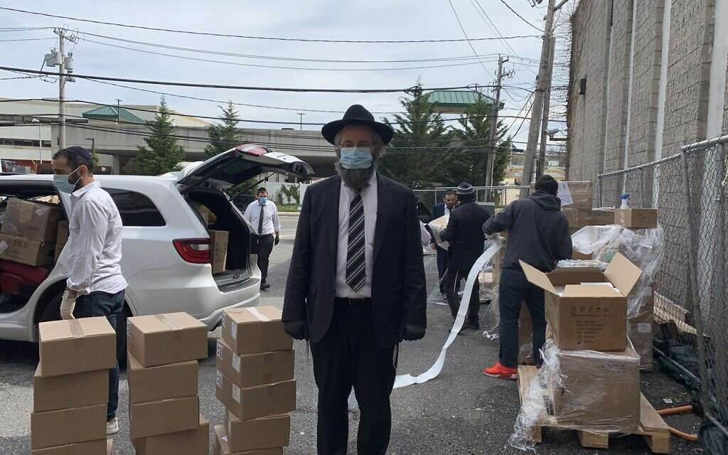 Rabbi Eitan Rubin with a delivery of personal protective equipment in the parking lot of Beit Midrash of Great Neck, New York. (Cathryn J. Prince/ Times of Israel)
