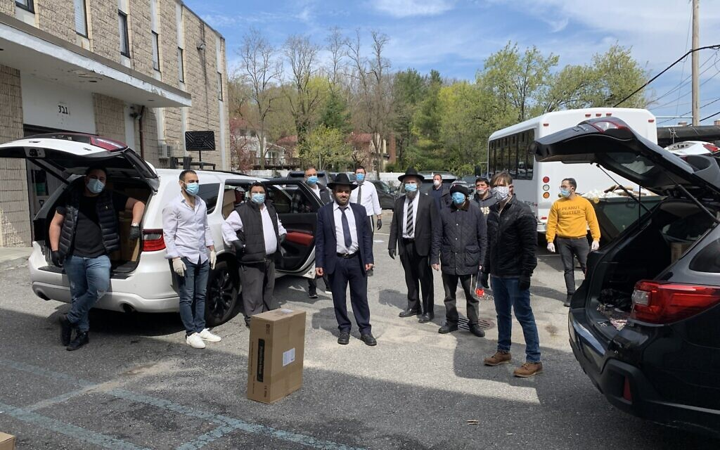 Rabbi Eitan Rubin, center, poses with volunteers including students and professionals as they load up personal protective equipment in the parking lot of Beit Midrash of Great Neck. (Cathryn J. Prince/ Times of Israel)