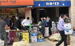 Residents of Beit Shemesh shop at a vegetable stand hours before the start of the Passover holiday. April 8, 2020. (Sam Sokol)