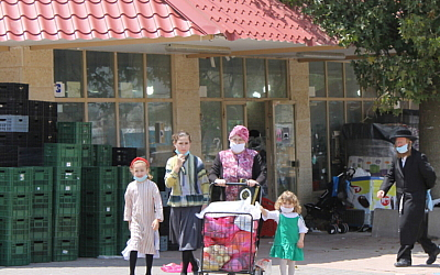 Residents walk in the Hasidic enclave of Ramat Beit Shemesh Bet under lockdown, April 27, 2020. (Sam Sokol/Times of Israel)