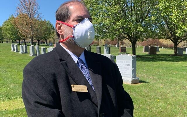 Glenn Easton, executive director of the Garden of Remembrance cemetery in Clarksburg, Maryland, watches the funeral of Anna Grosz on Wednesday April 22, 2020 (Courtesy)