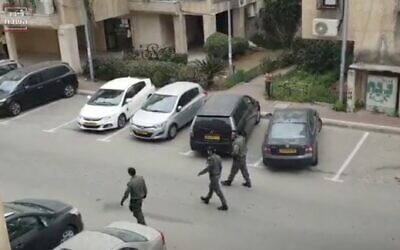 Police officers are seen outside the Bnei Brak home of Rabbi Tzvi Friedman ahead of the funeral of his wife Aliza on April 1, 2020. (Screen capture: Kikar HaShabbat)