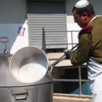 An IDF non-commissioned officer dips a pot in boiling water to prepare it for the Passover holiday in a video produced by the Military Rabbinate in 2014. (Screen capture: Youtube)