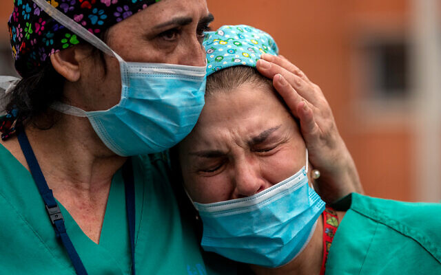 Health workers cry during a memorial for their co-worker that died of the coronavirus at the Severo Ochoa Hospital in Leganes in Leganes, Spain, April 10, 2020. (AP/Manu Fernandez)