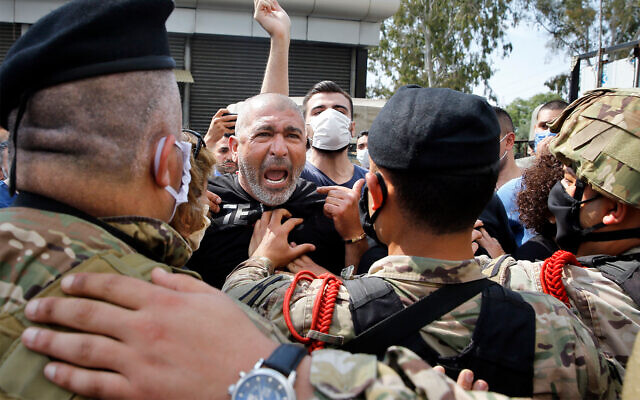 Anti-government protesters scuffle with Lebanese army soldiers in the town of Zouk Mosbeh, north of Beirut, Lebanon, April 27, 2020. (AP/Bilal Hussein)