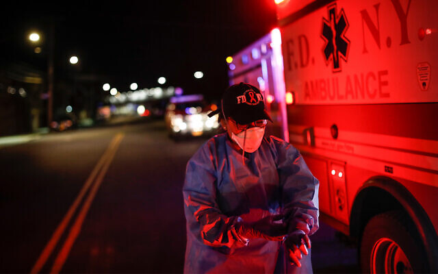 A paramedic suits up in personal protective equipment on an emergency call for a man in the Bronx, New York, April 15, 2020. (AP/John Minchillo)