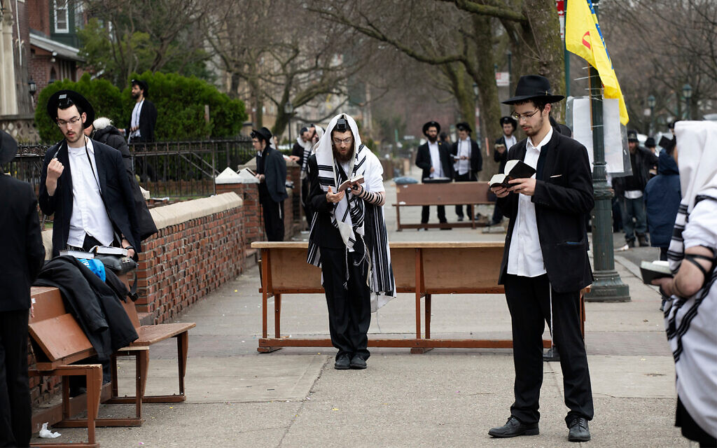Ultra-Orthodox Jewish men use social distancing as they pray outside the Chabad Lubavitch World Headquarters, in Brooklyn, New York, March 20, 2020. (AP/Mark Lennihan)
