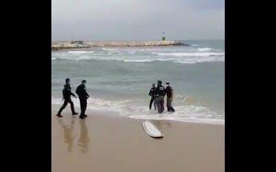 Police detain a surfer who allegedly refused to leave the water despite coronavirus regulations, April 24, 2020. (Screenshot/Twitter)