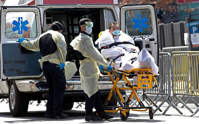 A patient is wheeled out of Elmhurst Hospital Center to a waiting ambulance, in the Queens borough of New York, April 7, 2020. (AP/Kathy Willens)