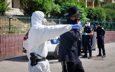 Israeli police officers remove ultra-Orthodox men from a yeshiva in Bnei Brak, April 2, 2020. (Flash90)