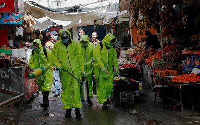 Workers wearing protective gear spray disinfectant as a precaution against the coronavirus at the main market in Gaza City, March 27, 2020. (AP/Adel Hana)