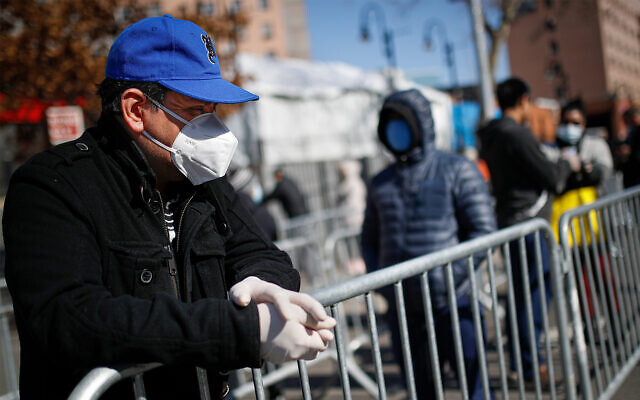 A patient wears a protective mask and gloves while waiting for COVID-19 testing outside Elmhurst Hospital Center, in New York, March 27, 2020. (AP/John Minchillo)