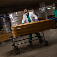 Workers move a coffin with the body of a coronavirus victim at a morgue in Barcelona, Spain, April 2, 2020. (AP/Emilio Morenatti)