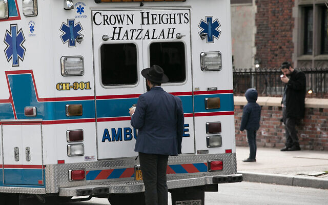 A man prays next to an idle ambulance in the Crown Heights neighborhood of Brooklyn, New York, April 7, 2020. (AP/Mark Lennihan)