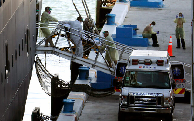 A person on a stretcher is removed from Carnival's Holland America cruise ship Zaandam at Port Everglades during the coronavirus pandemic, April 2, 2020, in Fort Lauderdale, Florida. (AP Photo/Lynne Sladky)