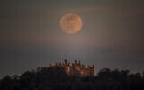 A supermoon is seen over Belvoir castle in Leicestershire, England, Tuesday, April 7, 2020. (Danny Lawson/PA via AP)