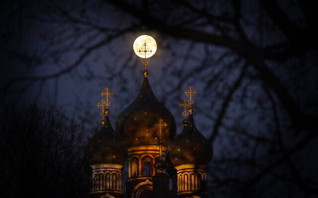The supermoon rises behind an illuminated cross from a Christian Orthodox church in Moscow, Russia, April 7, 2020. (AP/Alexander Zemlianichenko)