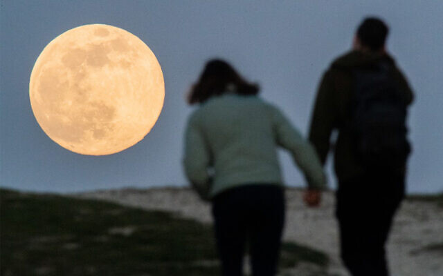 A couple hold hands as they walk to watch the supermoon come up in Hanover, western Germany, April 7, 2020. (Julian Stratenschulte/dpa/AFP)