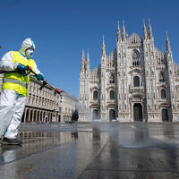 A worker sprays disinfectant to sanitize Duomo square in downtown Milan, Italy, March 31, 2020. (AP/Luca Bruno)