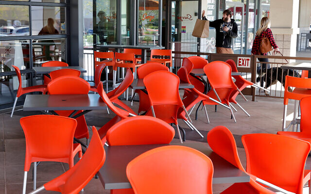 A couple picks up food at an empty restaurant in Phoenix, Arizona, March 27, 2020. (AP/Matt York)